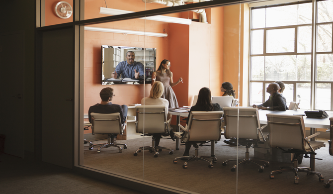 conference room with several participants watching a woman present and one remote participant on video conference
